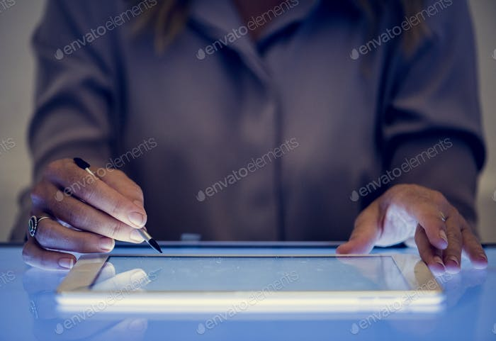 Hands holding using digital tablet on a cyber space table