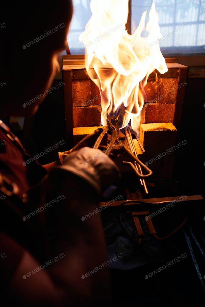 Putting metal in heated furnace