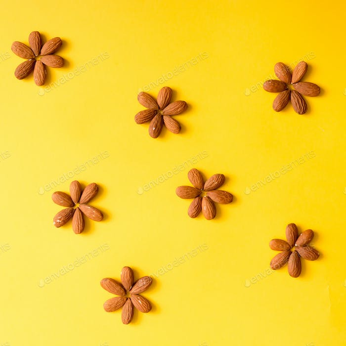 Creative arrangement of nuts on yellow background.