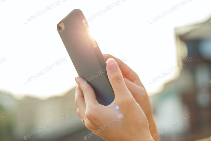 Woman use of mobile phone with sun flare