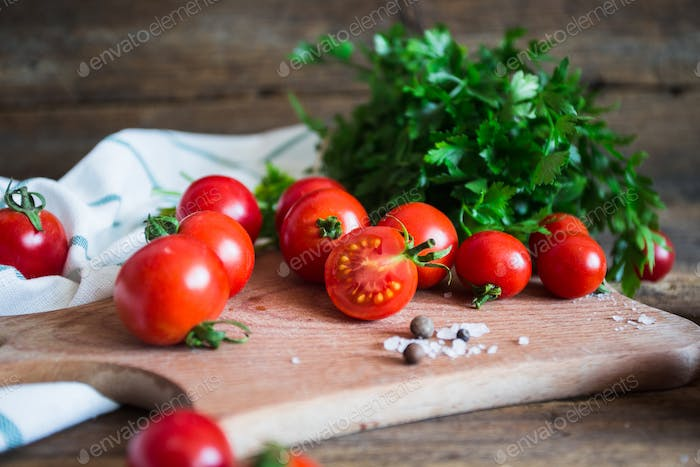 Fresh tomatoes with herbs on a kitchen board