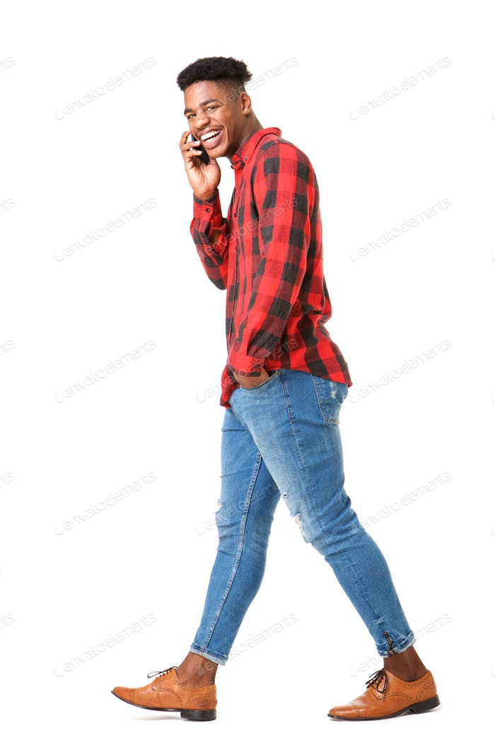 Full body side of happy african man walking and talking with mobile phone