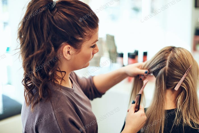 Hairdresser styling a client's hair in her salon