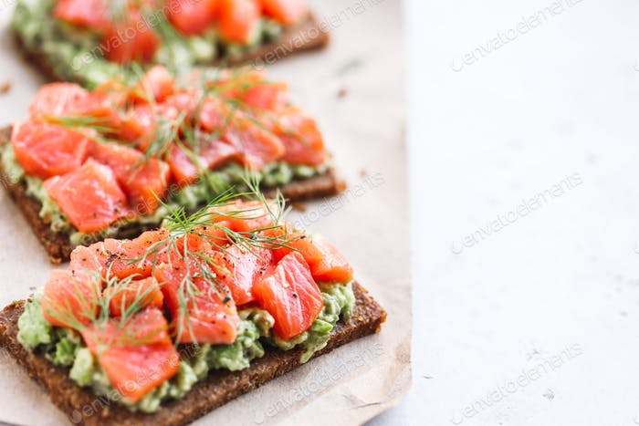 Close-up view of three sandwiches with rye bread, avocado and smoked salmon