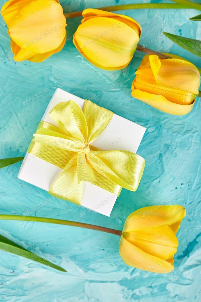 Gift box with yellow ribbon near tulip