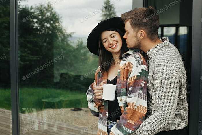 Happy young family of homeowners, enjoying morning in new home in woods