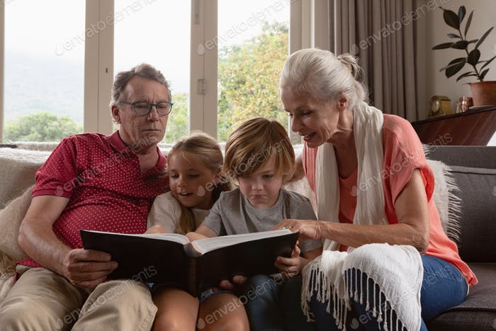 Front view of multi-generation Caucasian family looking at photo album on sofa in a comfortable home