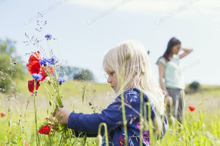Girl holding wildflowers at grassy field