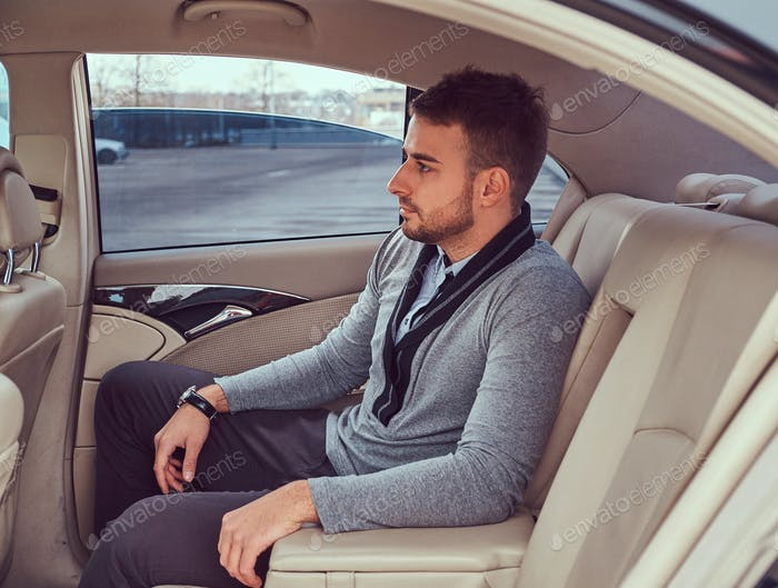 A handsome businessman in luxury car