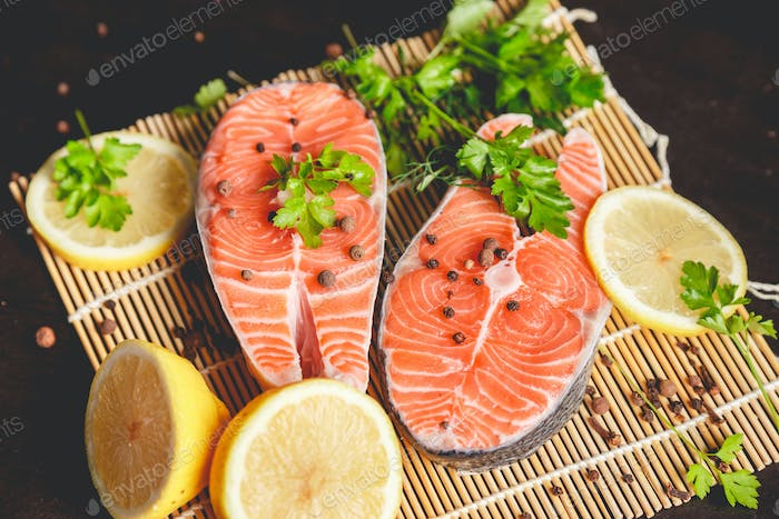 Salmon steaks with lemon, spices and spoon with salt