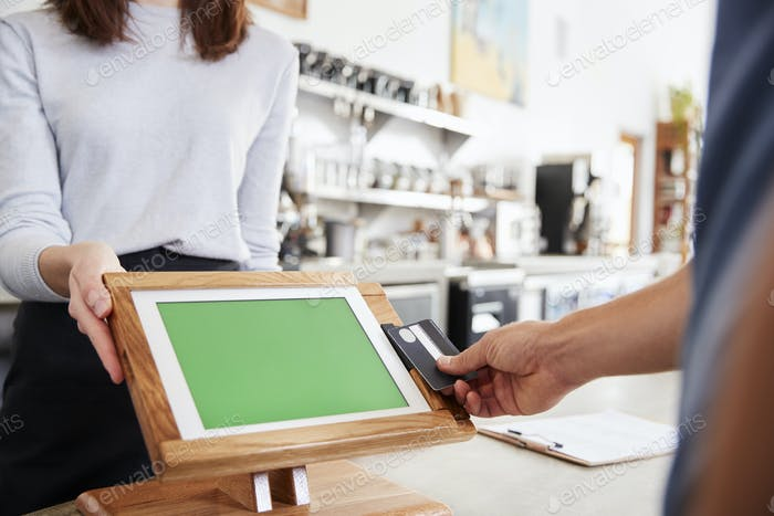 Customer making contactless card payment at cafe, close up