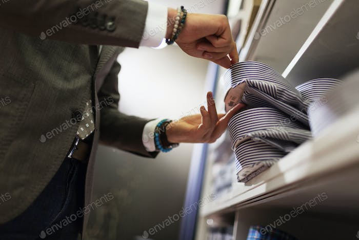 Midsection of sales clerk removing shirt from shelf in clothing store
