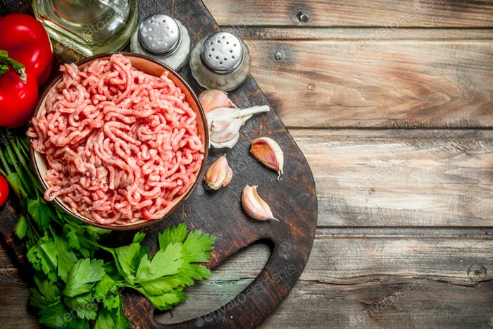 Raw minced meat in a bowl with parsley, tomatoes and garlic.
