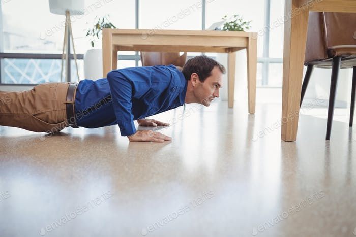 Determined executive doing push-ups