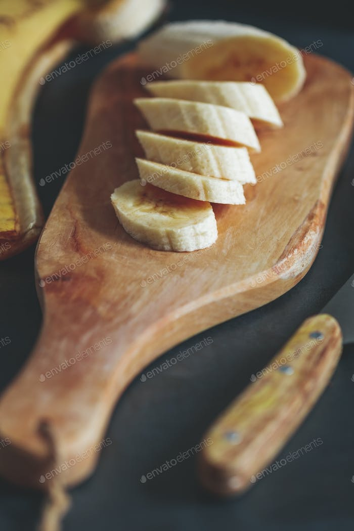 Chopped banana on a rustic wooden board over black table.