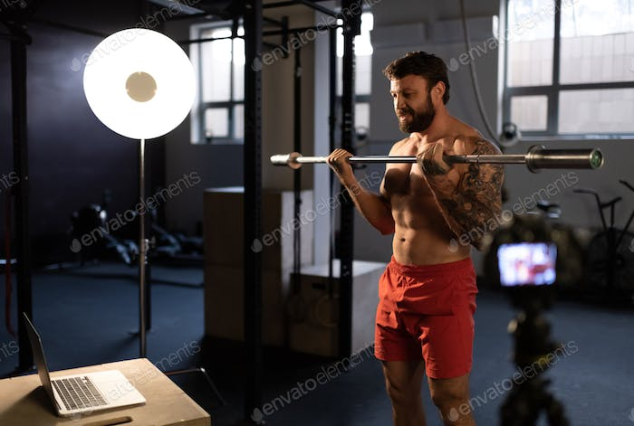 Athlete lifting barbell near laptop and camera