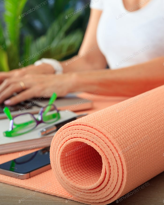 Woman and an exercise mat, corporate office background