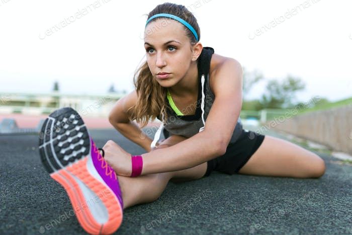 Beautiful young woman stretching and preparing for running on tr