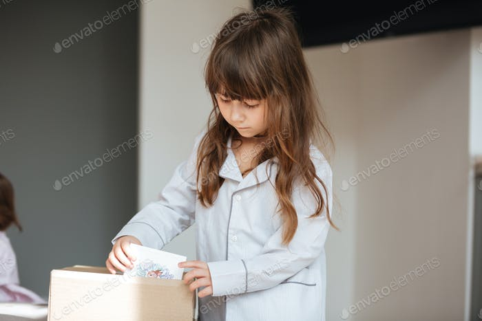 Little child getting out of package postcards