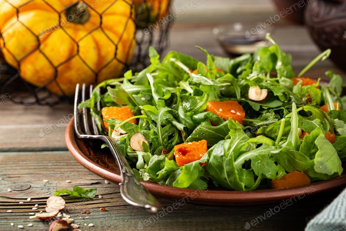 Delicious salad with arugula and baked pumpkin