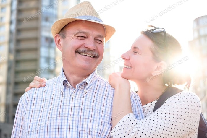 Hispanic father in summer hat and daughter walking outdoor together.