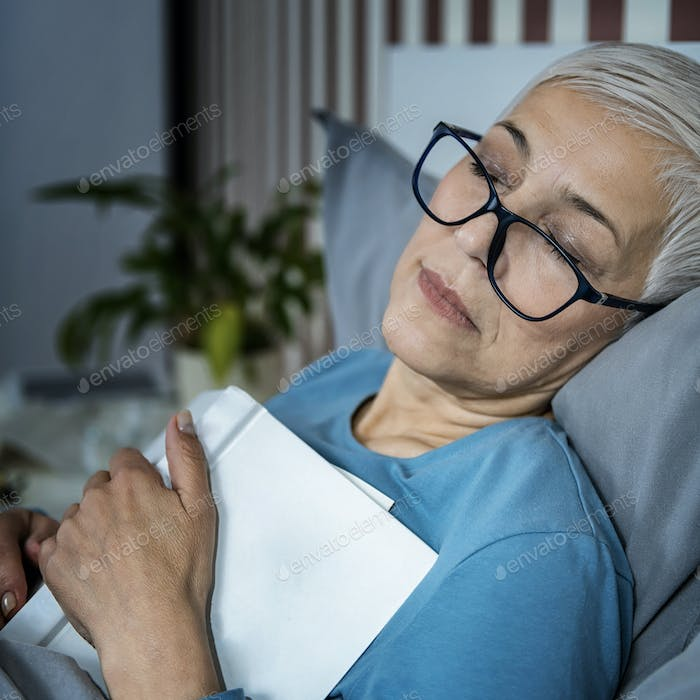 Sleep. Senior Woman Falling Asleep with a Glasses on and a Book on her Chest