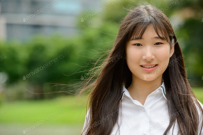 Happy young beautiful Asian teenage girl at the park
