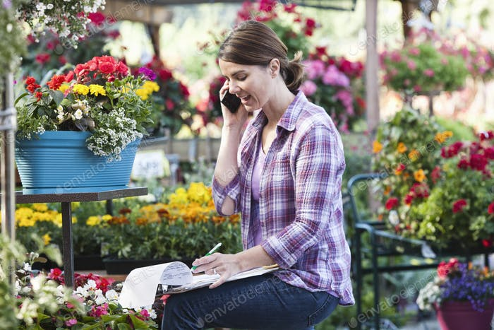 Caucasian woman employee of a nursery ordering supplies on the phone.