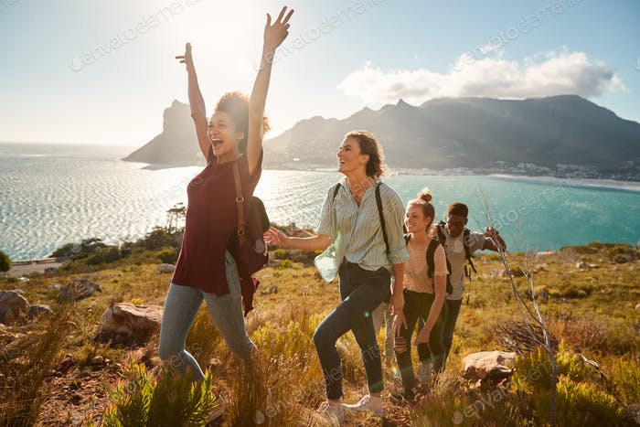 Young adult friends hiking single file uphill celebrate reaching a summit, full length, side view