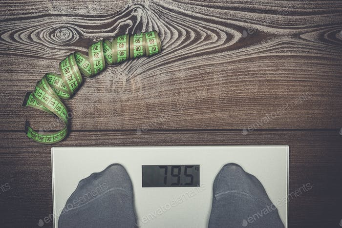 electronic scales on the wooden floor dieting concept