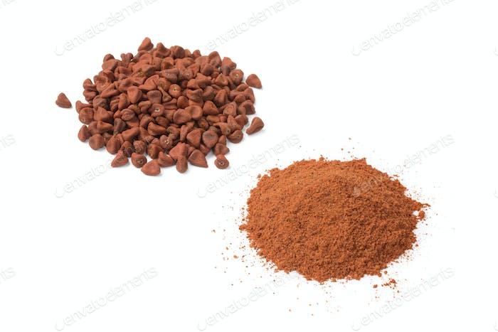 Heap of dried Annatto seeds and a heap of ground Annatto  powder