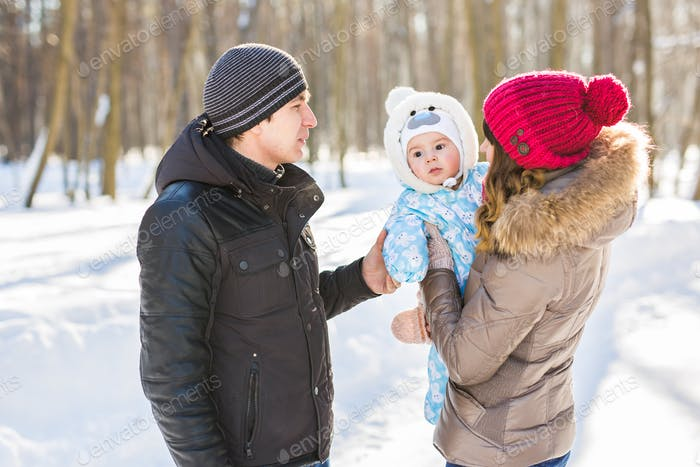 parenthood, season and people concept - happy family with child in winter clothes outdoors