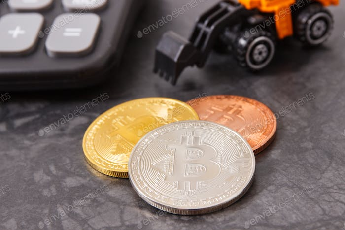 Bitcoin coins with calculator and miniature excavator