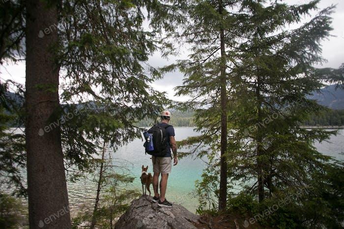 Mann mit Rucksack und Hund am Rande des Waldsees