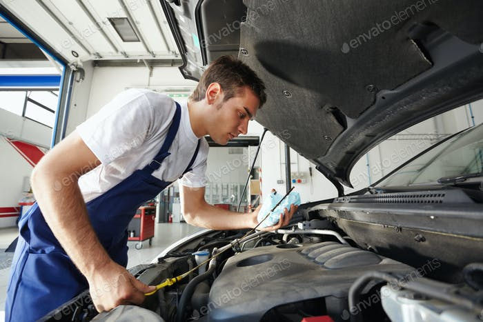 Man Working In Car Repair Shop As Mechanic Reviewing Engine Oil