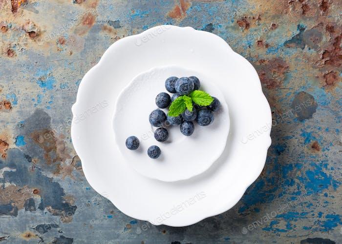 Frisch gepflückte Heidelbeeren auf weißem Teller