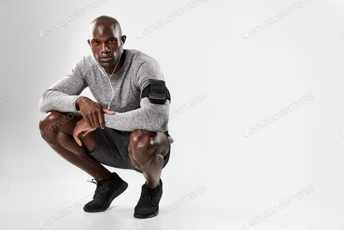 Fit young african man crouching over grey background