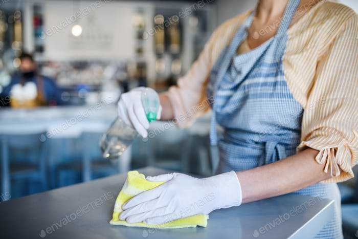 Unrecognizable woman working with gloves in coffee shop, disinfecting tables
