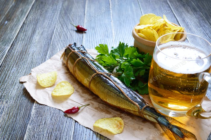 Beer snacks. Smoked fish, chips, a glass of lager beer on a wooden table.