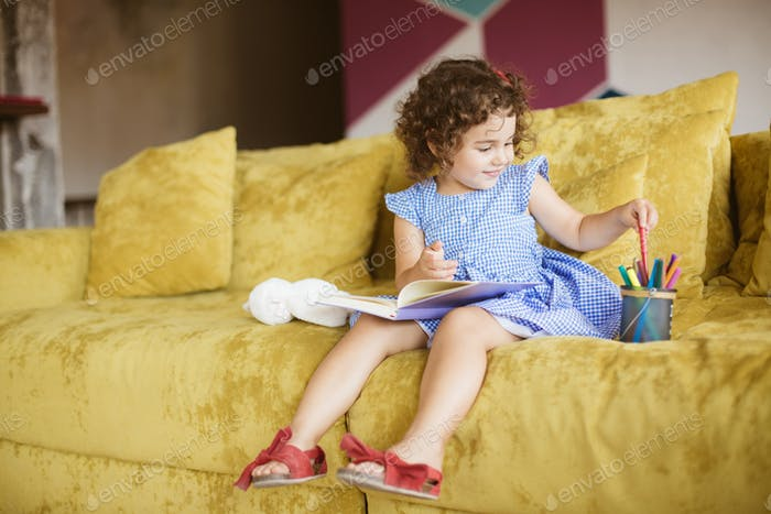 Cute smiling baby girl with dark curly hair in dress with book o
