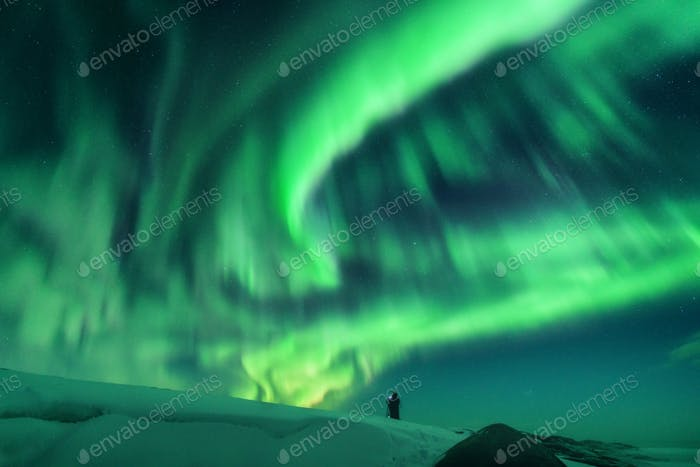 Aurora borealis and silhouette of a man on the hill