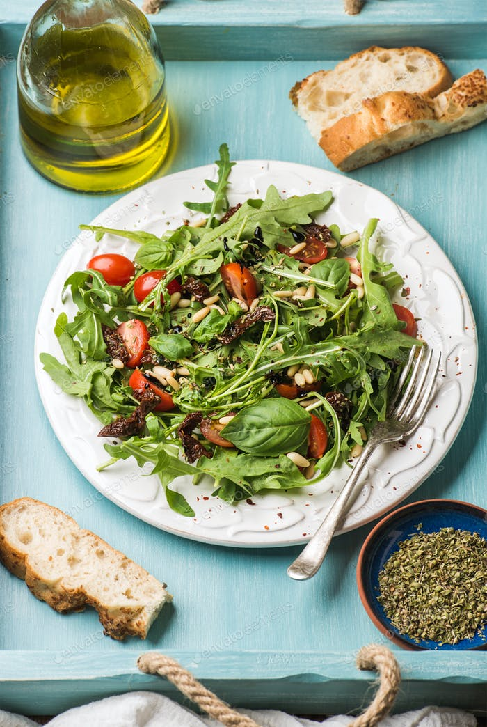 Salad with arugula, cherry tomatoes, pine nuts and herbs