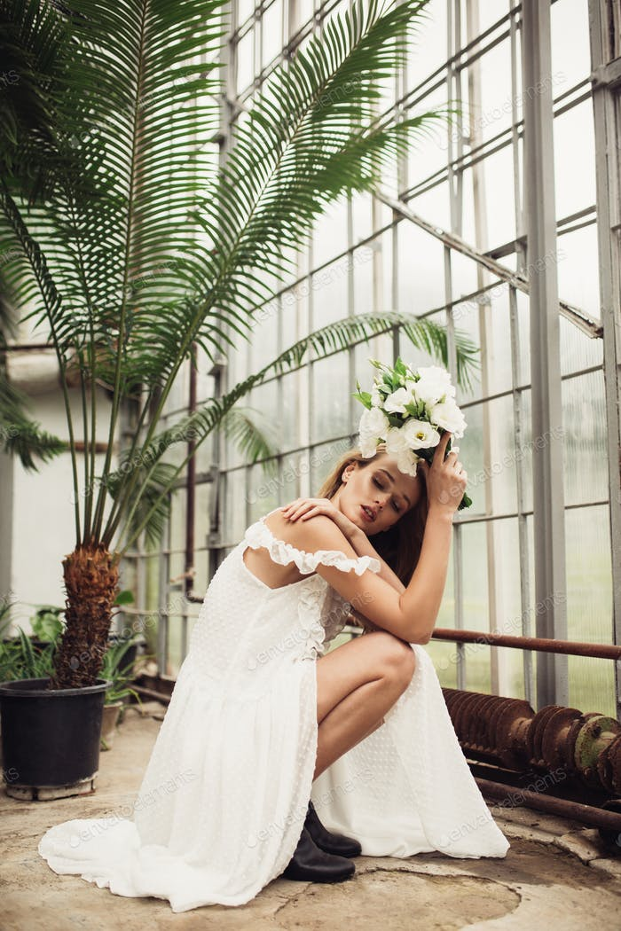 Young attractive bride in white dress sitting down holding littl