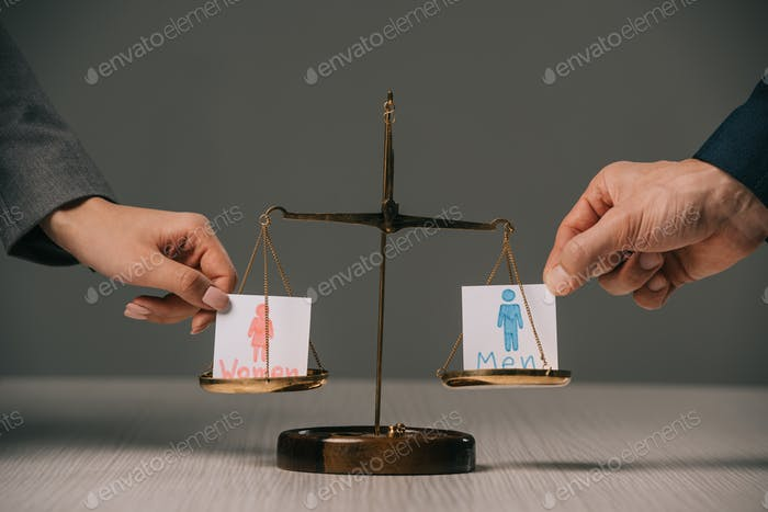 cropped view of businesspeople with male and female signs on scales of justice, gender equality