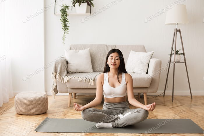 Morning Meditation. Asian Girl Practicing Yoga at Home