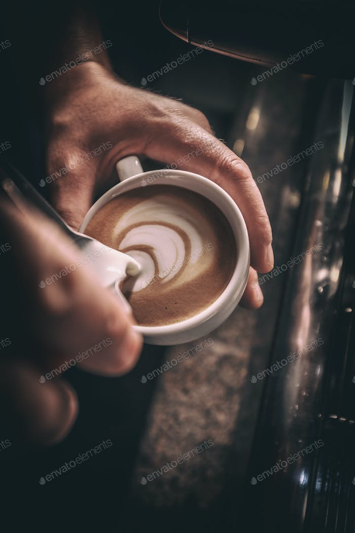 Barista pours milk