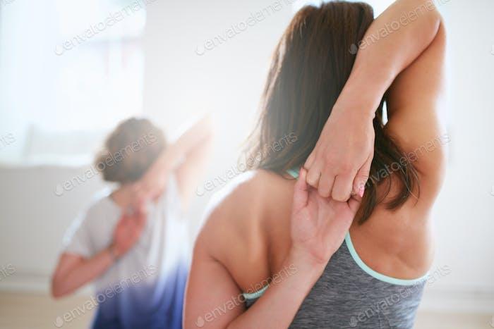 Fit woman doing gomukhasana in yoga class