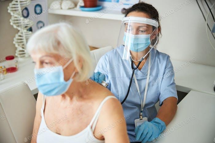 Persona médica que mueve una pieza de pecho de estetoscopio en la espalda femenina