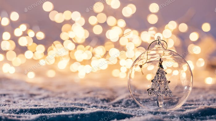Christmas glass ball with tree in it on winter background.