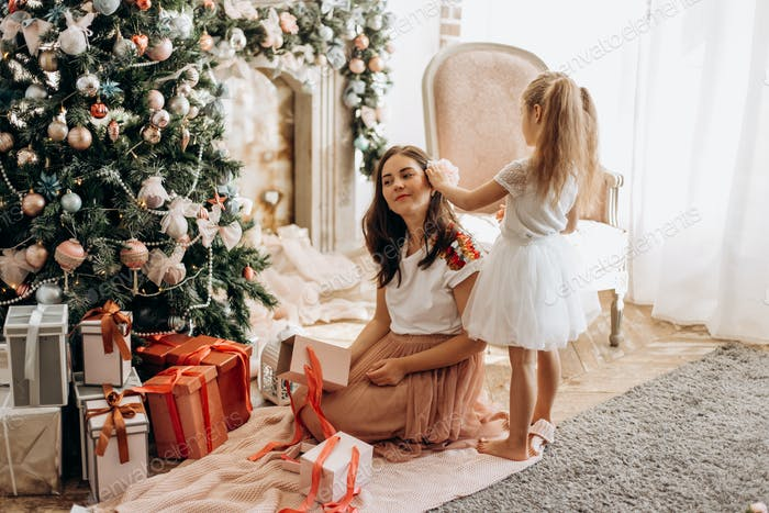 Glückliche junge Mutter und ihre kleine Tochter in schönen Kleid sitzen ne